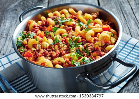 close-up of american italian goulash of elbow pasta, beef, celery and tomatoes in a metal saucepan on a rustic wooden table with napkin, view from above #1530384797