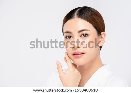 Youthful radiant pretty Asian woman with hand touching face on white background for beauty and skin care concepts Royalty-Free Stock Photo #1530400610
