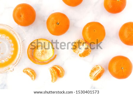 Clementines, clementine segments and juice in a citrus juicer on white marble background. Top view. #1530401573