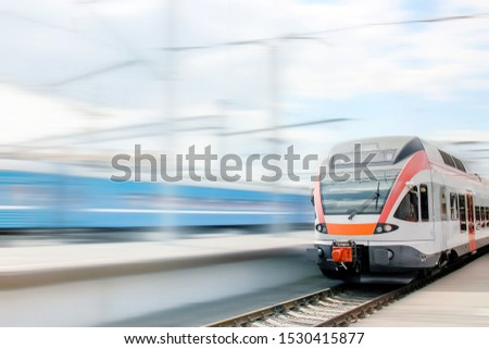 Beautiful railway station with modern gray-red commuter train in Minsk, Belarus. Train on railroad track with motion blur effect by day. Railway platform. Industrial landscape. Railway tourism #1530415877