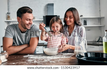 Cute little girl and her beautiful parents are knead flour for baking and smile while cooking in the kitchen. #1530423917