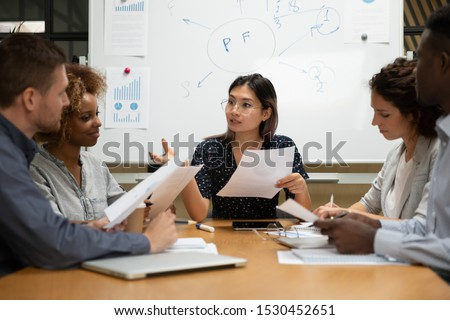 Multi-ethnic team led by asian ethnicity female ceo sitting at boardroom desk holding documents discussing stats, make assess credit worthiness of business, doing financial statement analysis concept #1530452651