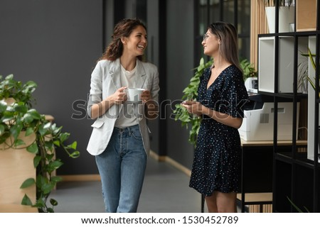 Asian and Caucasian ethnicity women colleagues met in office hall chatting enjoy friendly warm conversation, multi-ethnic mates having informal talk drink tea or coffee take break distracted from work #1530452789