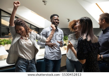 Friendly different ethnicity young office workers feeling happiness celebrating financial success or career growth, multi-ethnic colleagues standing in co-working space dancing enjoy Friday concept #1530452813