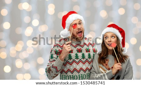 christmas, photo booth and holidays concept - happy couple in ugly sweaters posing with party props over festive lights background
