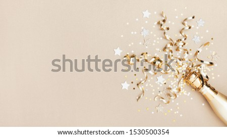 Celebration background with golden champagne bottle, confetti stars and party streamers. Christmas, birthday or wedding concept. Flat lay. #1530500354