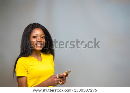 satisfied Young African hipster girl,types text message on cell phone, enjoys online communication, types feedback, wears yellow shirt, isolated on Gray studio wall. Technology concept #1530507296