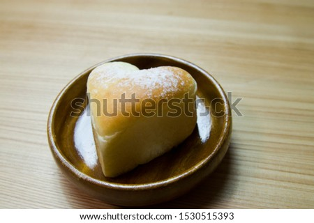 This is a heart-shaped bread.   A heart-shaped bread is on the table. #1530515393