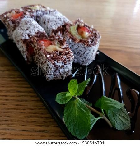Macro photo sweet sushi rolls with mint. Stock photo dessert sweet sushi set with fruits