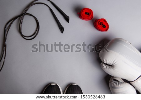 Combat sport equipment: boxing gloves, jump rope and hand bands. Sport accessories, grey background, top view, copy space Royalty-Free Stock Photo #1530526463