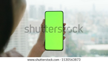asian woman hold 5g full display phone with green screen #1530563873