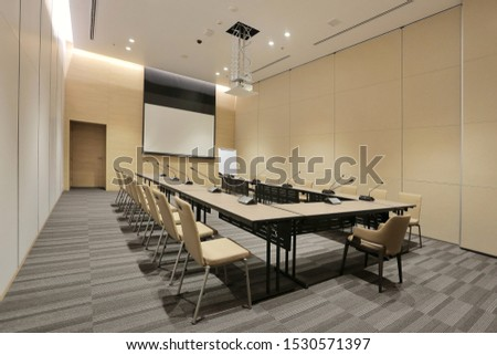 Interior of modern fully equipped professional facilities meeting conference room boardroom classroom office with nobody empty and  microphones white projector board chairs door business meeting venue #1530571397
