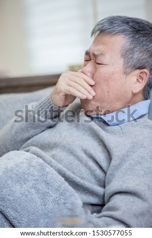 asian eldely man get sick and cough lying on the sofa at home #1530577055