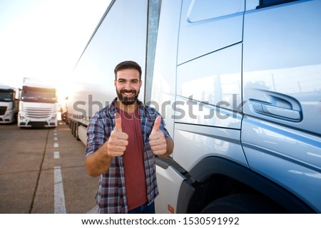 Middle aged professional trucker holding thumbs up and standing by his truck. Happy truck driver. Transportation services. #1530591992