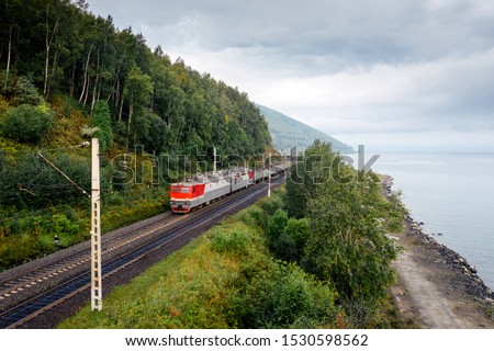 Freight train on the railroad of Trans-Siberian Railway on the shore of Baikal Lake with green forest trees and cloudy sky. East Siberian Railway in Buryatia, Siberia, Russia #1530598562