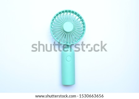 Portable rechargeable mini fans. Close-up of tosca portable fans. Standing position on white background. Landscape mode captured.