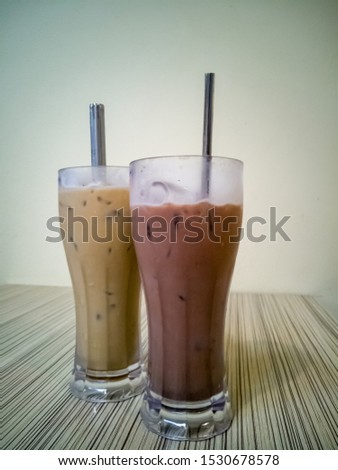 Close up on a tumbler glass full of iced coffee with a reusable metal drinking straw, on a wood restaurant table #1530678578