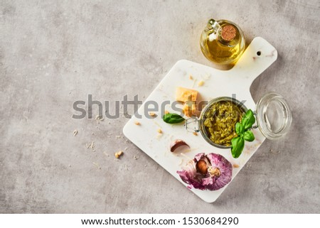 Pesto sauce or pesto genovese in a glass jar with pine nuts, parmesan, basil, oil and garlic on white marble cutting board over grey stone background. Top view. Copy space. #1530684290