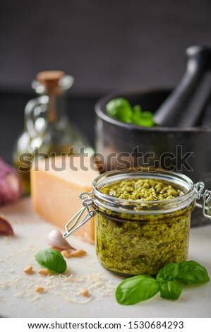 Pesto sauce or pesto genovese in a glass jar with pine nuts, parmesan, basil, oil and garlic on white marble cutting board. Copy space. #1530684293