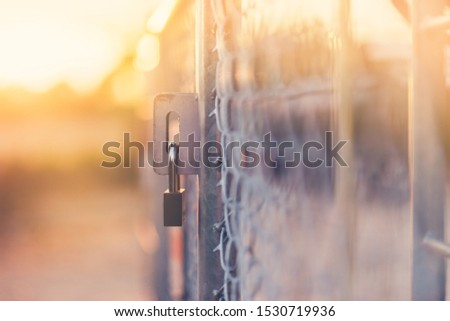 Steel cage locking padlock with flare light and sunlight  and blur background. #1530719936