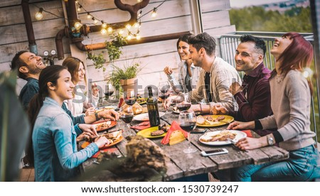 Young people dining and having fun drinking red wine together on balcony rooftop dinner party - Happy friends eating bbq food at restaurant patio - Millennial life style concept on warm evening filter #1530739247