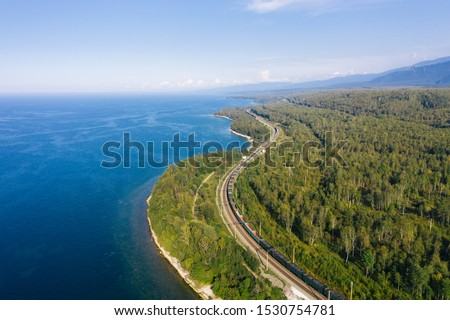 Aerial view of a freight train on the railroad of Trans-Siberian Railway on the shore of Baikal Lake with green forest trees in a sunny summer day. East Siberian Railway in Buryatia, Siberia, Russia #1530754781