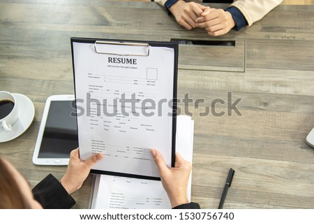 Close up view of job interview in office, focus on resume writing tips, employer reviewing good cv of prepared skilled applicant, recruiter considering application, hr manager making hiring decision. #1530756740
