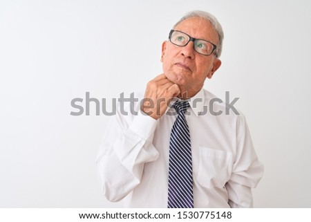Senior grey-haired businessman wearing tie and glasses over isolated white background with hand on chin thinking about question, pensive expression. Smiling with thoughtful face. Doubt concept. #1530775148