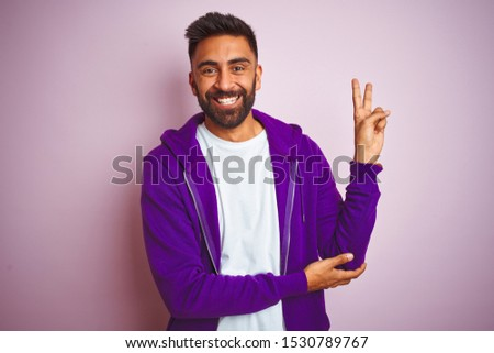 Young indian man wearing purple sweatshirt standing over isolated pink background smiling with happy face winking at the camera doing victory sign. Number two. #1530789767