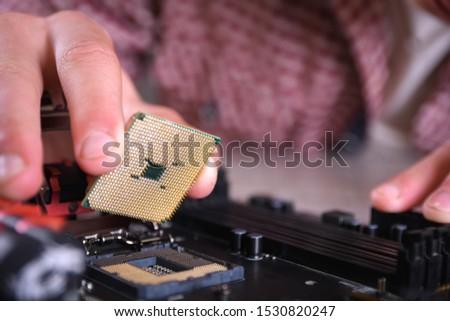 Man repairing broken computer, video card,memory RAM, cooler, processor,hard drive. Young repairer working with screwdriver in service center.teenager #1530820247