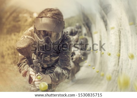 Woman paintball player in camouflage and mask aiming with gun in shootout on battlefield #1530835715