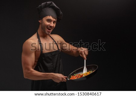 Young male cook in a black apron and hat cooks vegetables in a pan. #1530840617
