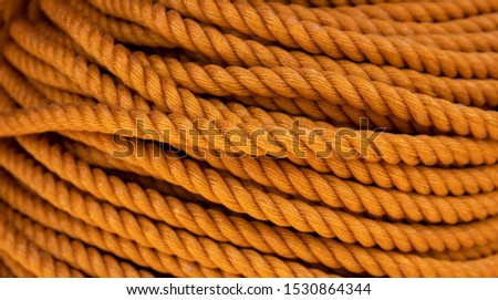 Yellow cord background, close-up photo. Braided rope texture. Ship or rock climbing tackle. Natural material woven cordage. Simple rope bulk concept. Alpine mountaineering equipment. Safety orang rope #1530864344