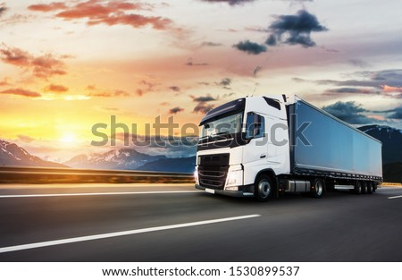 European truck vehicle on motorway with dramatic sunset light. Cargo transportation and supply theme. #1530899537