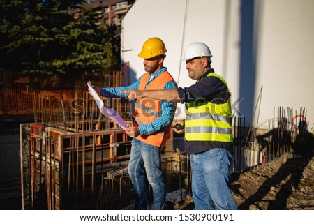 Men in hardhat and yellow and orange jacket posing on building site. stock photo