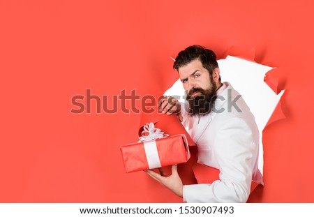 Through paper. Bearded man holds gift box. Valentine's day. Christmas. New year. Birthday. Holidays concept. Man with christmas gift. Attractive man with gift. Businessman holds gift box. Copy space. #1530907493