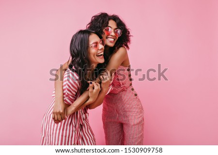 Amazing, beautiful lady rejoice and enjoy photo shoot in pink. African girls with curly hair in sunglasses laugh #1530909758