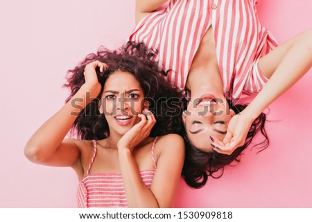 Young ladies with beautiful brown eyes and cute make-up, dressed in fashionable designer clothes of pink color, play in front of camera and demonstrate their emotions #1530909818