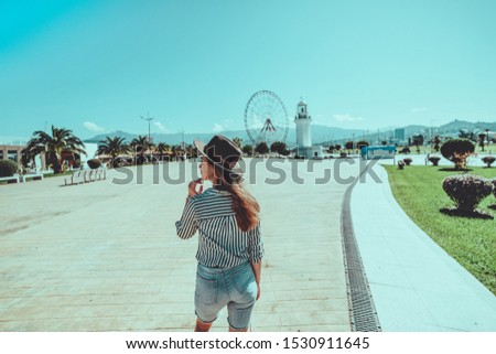 Woman traveler in a hat walks in the port at the ferris wheel in resort town Batumi, Georgia during vacation  #1530911645