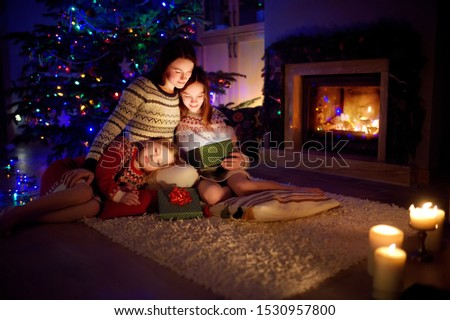 Happy young mother and her two small daughters opening a magical Christmas gift by a fireplace in a cozy dark living room on Christmas eve. Winter evening at home with family and kids. #1530957800