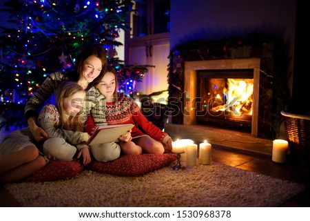 Mother and her two cute young daughters using a tablet pc at home by a fireplace in warm and cozy living room on Christmas eve. Winter evening at home with family and kids. #1530968378