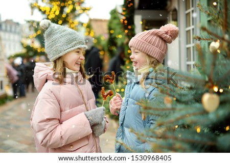 Two adorable sisters having rooster-shaped lollipops on traditional Christmas fair in Riga, Latvia. Children enjoying sweets, candies and gingerbread on Xmas market. Winter time with family and kids. #1530968405
