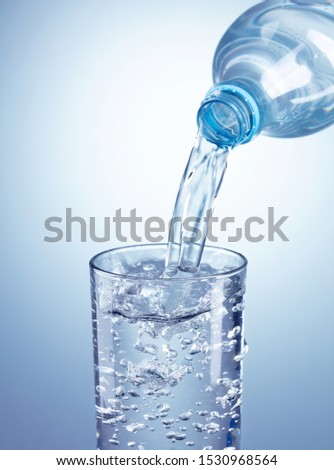 pouring water from plastic bottle into glass on light blue background #1530968564