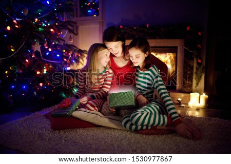 Happy young mother and her two small daughters opening a magical Christmas gift by a fireplace in a cozy dark living room on Christmas eve. Winter evening at home with family and kids. #1530977867