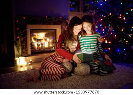 Happy young mother and her two small daughters opening a magical Christmas gift by a fireplace in a cozy dark living room on Christmas eve. Winter evening at home with family and kids. #1530977870