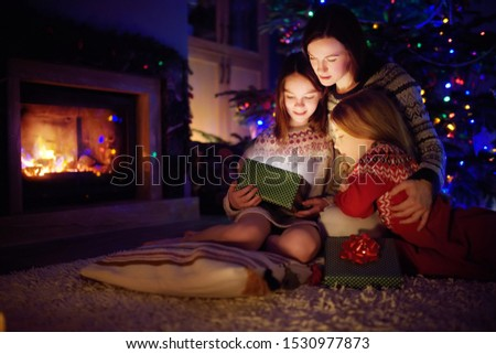 Happy young mother and her two small daughters opening a magical Christmas gift by a fireplace in a cozy dark living room on Christmas eve. Winter evening at home with family and kids. #1530977873