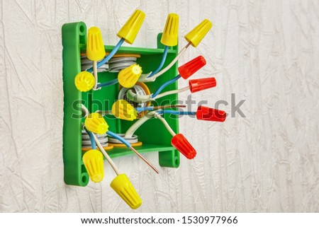 Screw-nut connection of electrical wire in home wiring. Installation of a plastic rectangular distribution box. Connecting wires by twisting into pigtails. #1530977966