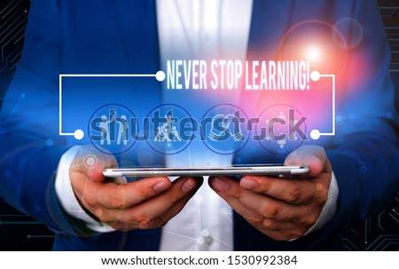 Text sign showing Never Stop Learning. Conceptual photo keep on studying gaining new knowledge or materials Male human wear formal work suit presenting presentation using smart device. #1530992384