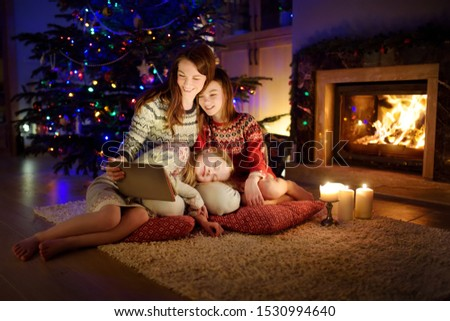 Mother and her two cute young daughters using a tablet pc at home by a fireplace in warm and cozy living room on Christmas eve. Winter evening at home with family and kids. #1530994640