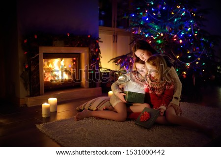 Happy young mother and her two small daughters opening a magical Christmas gift by a fireplace in a cozy dark living room on Christmas eve. Winter evening at home with family and kids. #1531000442